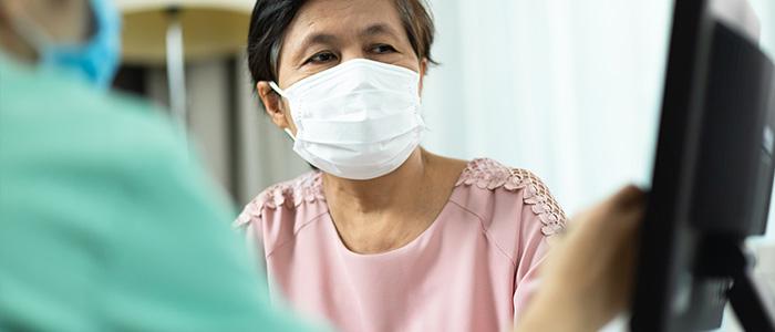 Mulher fazendo cadastro em sistema de reconhecimento facial usando máscara.