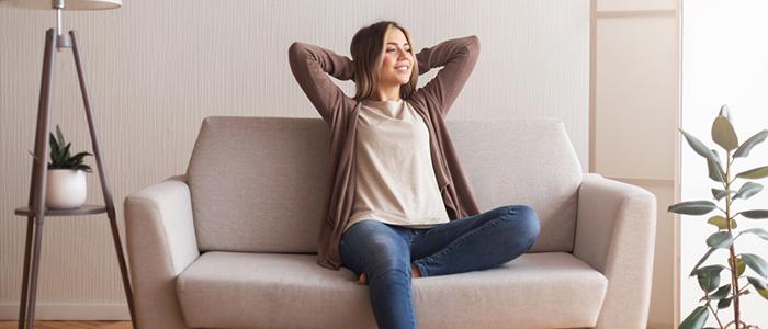 Mulher sentada em sofá, sorrindo e enquanto descansa.
