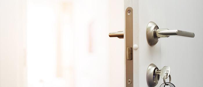 Porta branca, entreaberta, ilustrando onde a fechadura.