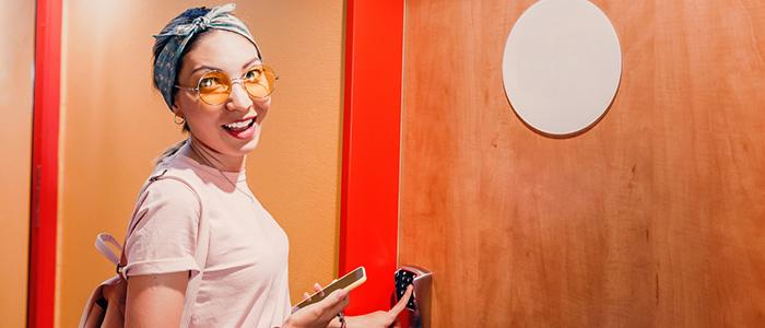 Mulher abrindo porta com fechadura eletrônica.