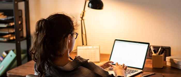 Mulher jovem, usando óculos de grau, trabalhando em home office.
