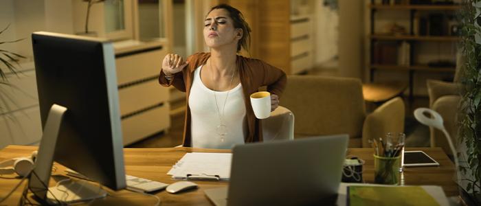 Mulher em home office, se espreguiçando.