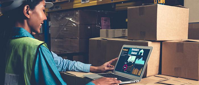 Automação comercial: Pessoa mexendo em notebook perto de caixas de estoque.