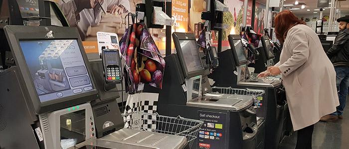 Automação comercial: Mulher usando self checkout em super mercado.
