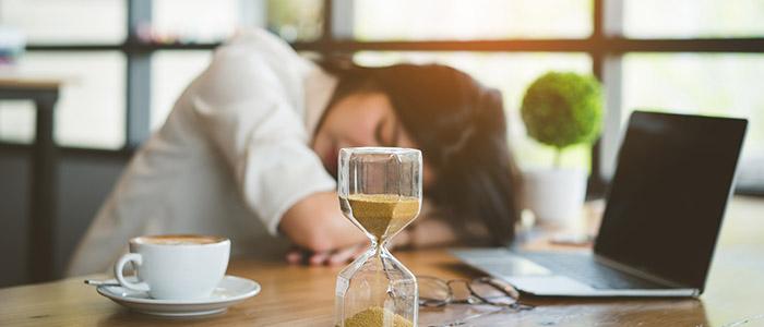 Mulher debruçada sobre mesa de trabalho, representando horas extras em home office.