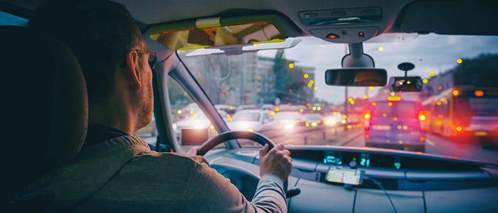 Motorista dirigindo em transito, fazendo horas extras.