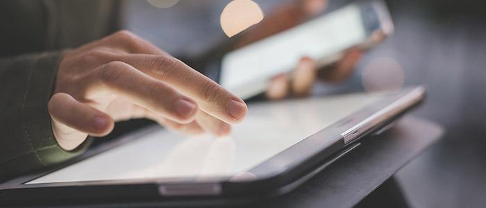 Ponto mobile: Pessoa mexendo em tablet e celular ao mesmo tempo.