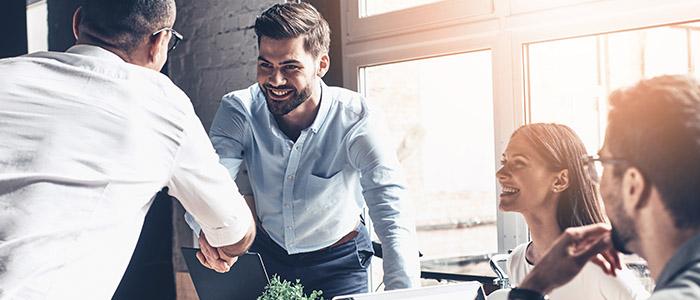 RH: Pessoas em escritório conversando, enquanto dois homens sorriem e apertam as mãos.
