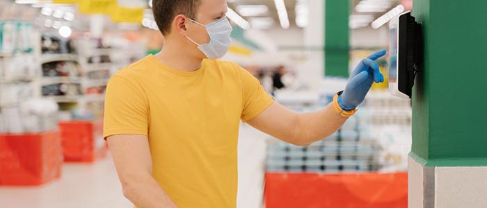 Homem de máscara e luvas no mercado usando o self checkout