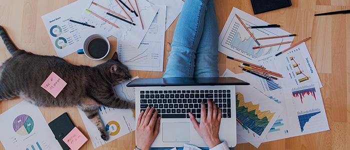 Trabalho remoto: Pessoa sentada no chão, mexendo em notebook.